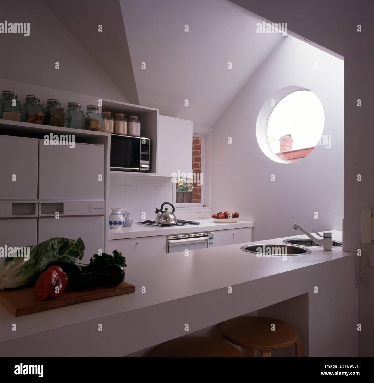 Rundes Fenster in kleinen, weißen neunziger Jahre Küche mit Gemüse ...