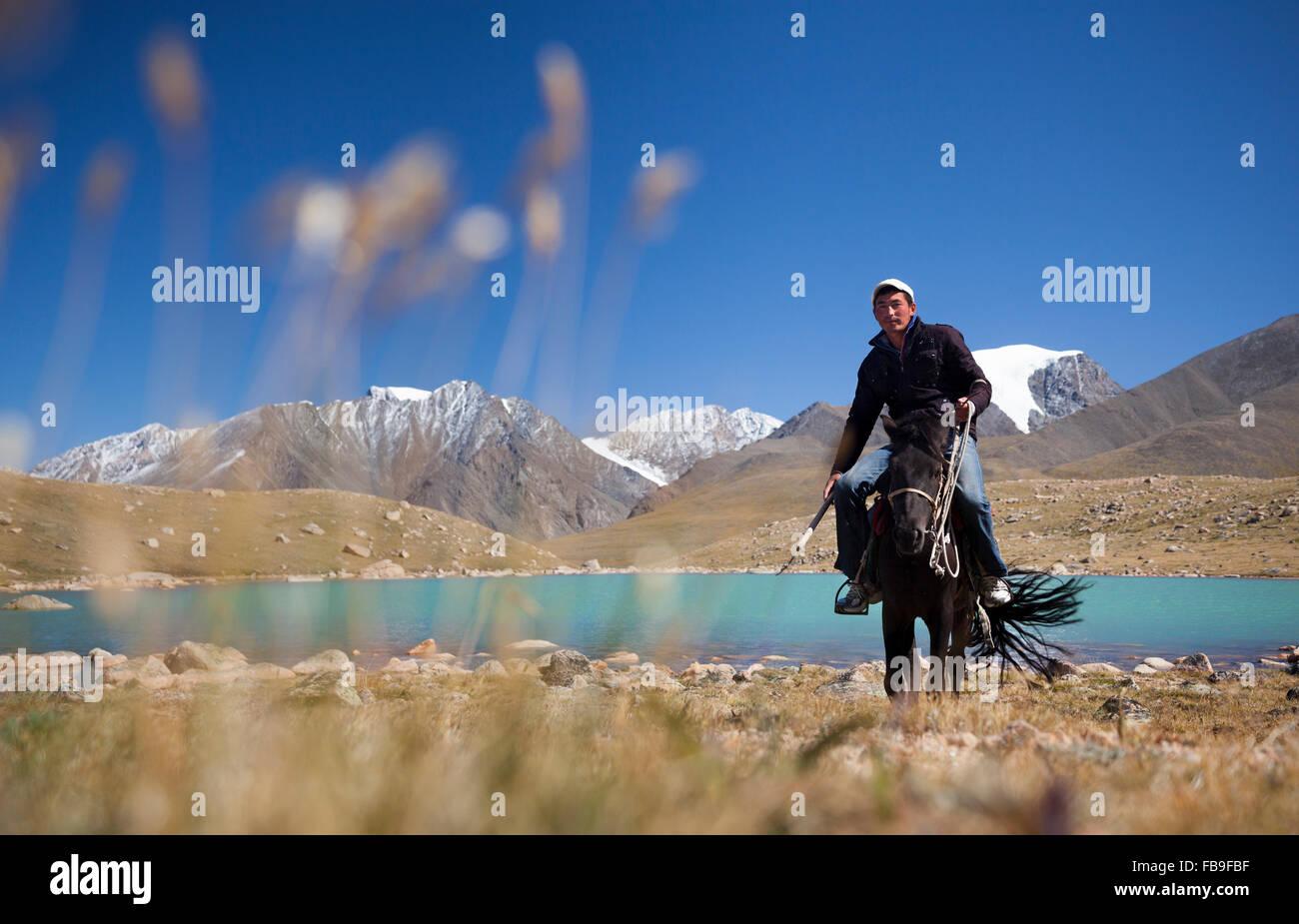 Tsaganaa, ein Führer und Herder, Reiten in der Nähe von einem Gletschersee in der abgelegenen Kharkhiraa Stockbild