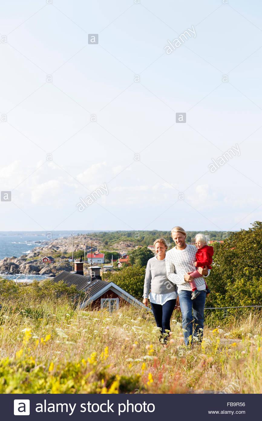 Schweden, Stockholmer Schären, Sodermanland, Oja, Frau und Mann zu Fuß durch Wiese mit Sohn (2-3) auf Händen Stockfoto