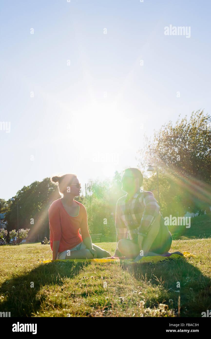 Finnland, Uusimaa, Helsinki, Kaivopuisto, junge Frau und Mann sitzt im Park auf sonnigen Tag Stockbild