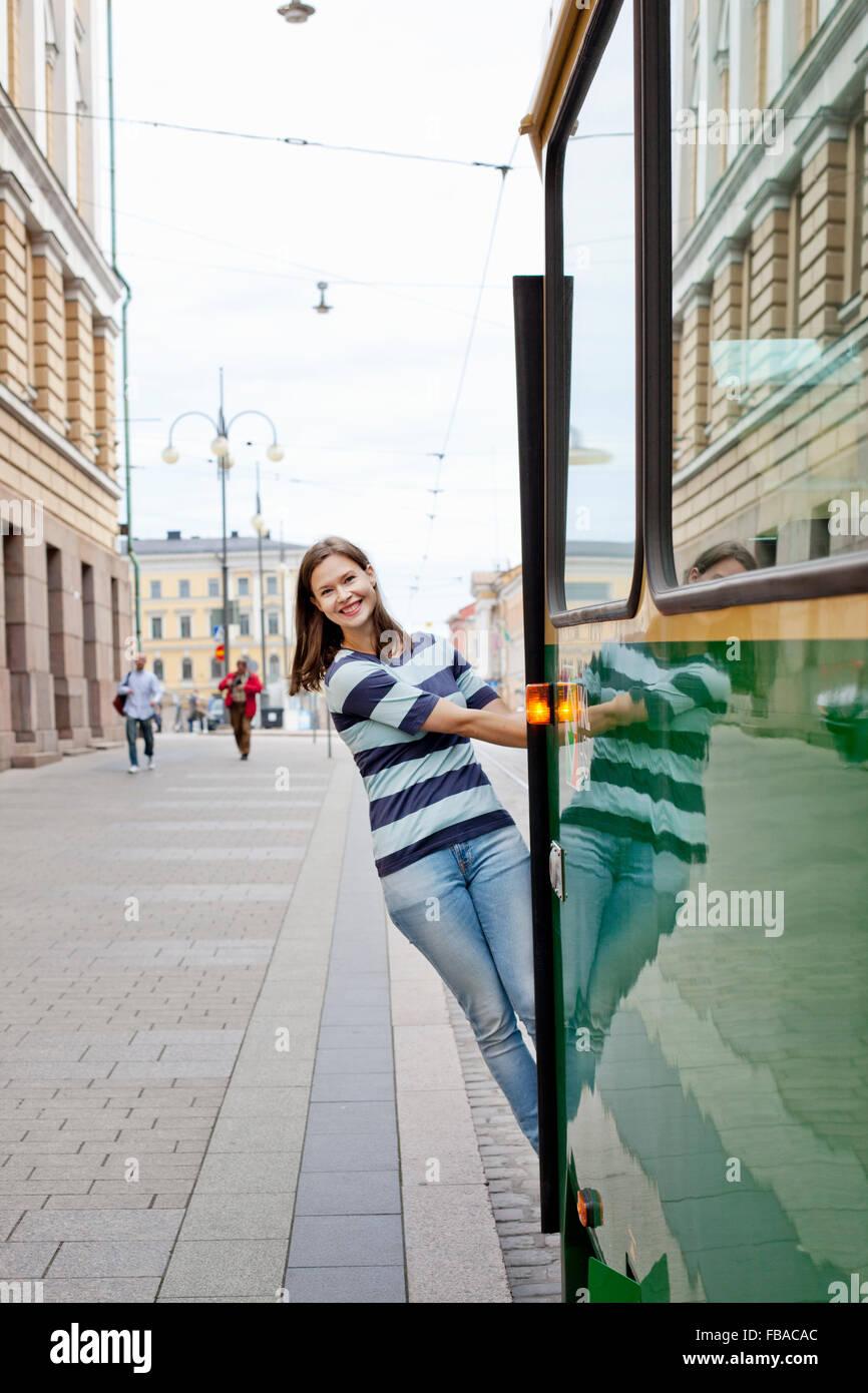 Finnland, Uusimaa, Helsinki, Kruunuhaka, junge Frau aus Straßenbahn gelehnt Stockbild