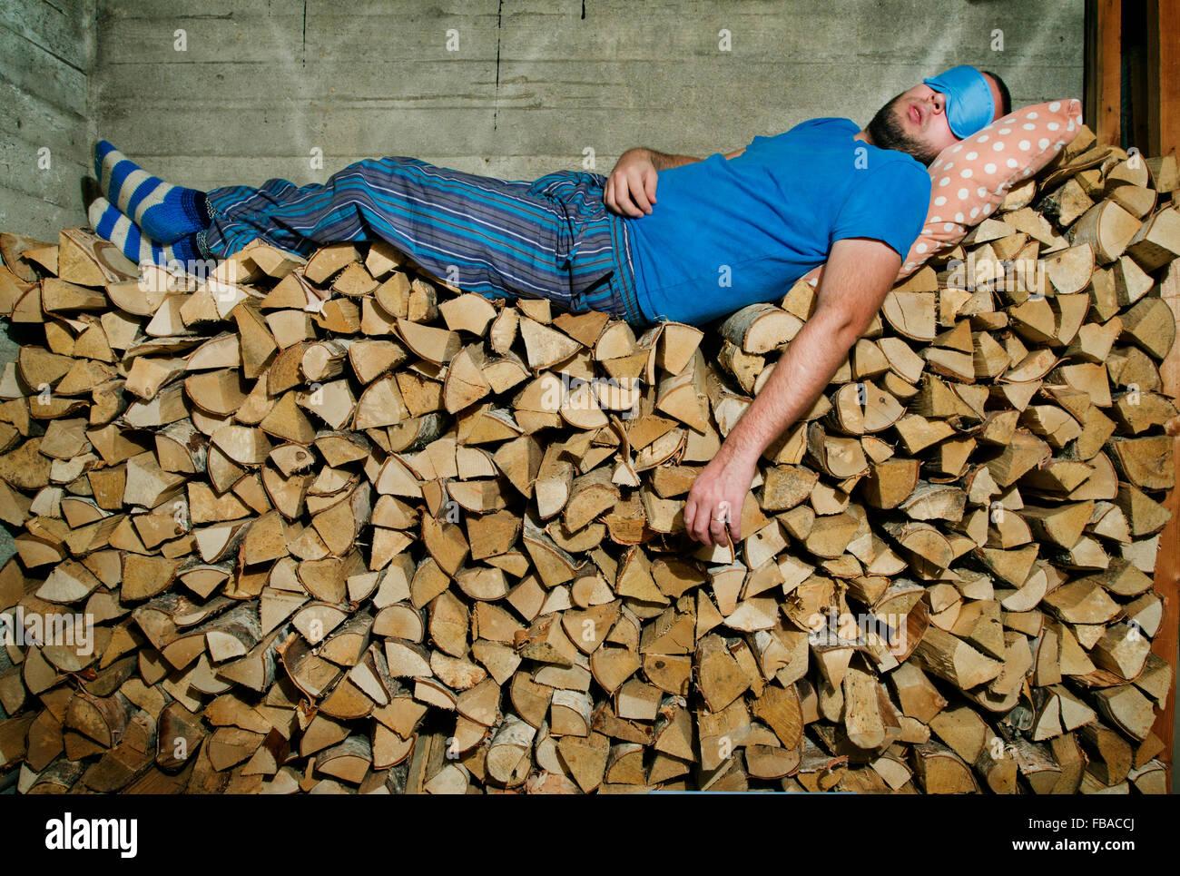 Heinola, Finnland Mann schlafen auf Haufen Brennholz Stockfoto