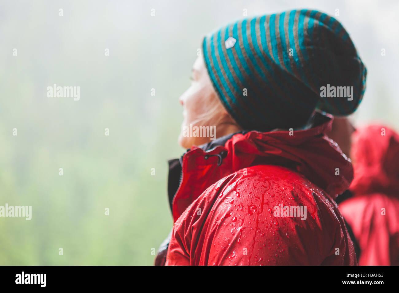 Schweiz, Ausserferrera, junge Frau trägt warme rote Jacke und Wollmütze Stockbild