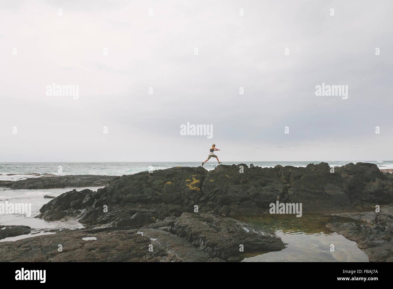 USA, Hawaii, Big Island, Mann springt über Geklüft Felsformation am Meeresstrand Stockbild