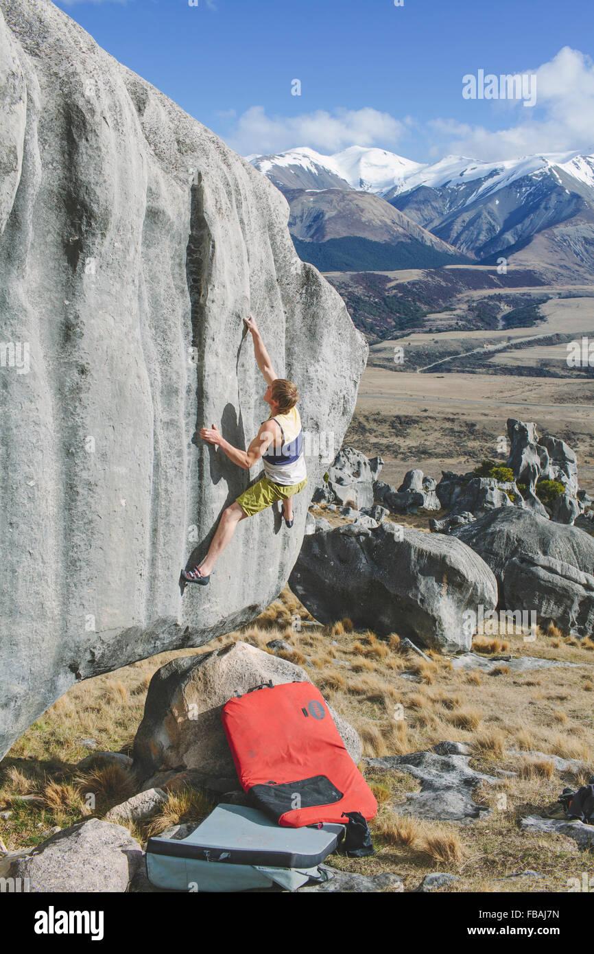 Neuseeland, Castle Hill, junger Mann Klettern auf Felsen mit schneebedeckten Bergen in Ferne sehen Stockbild