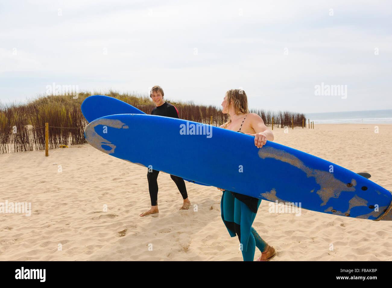 Portugal, Lissabon, zwei Menschen, die die Surfbretter am Strand Stockbild