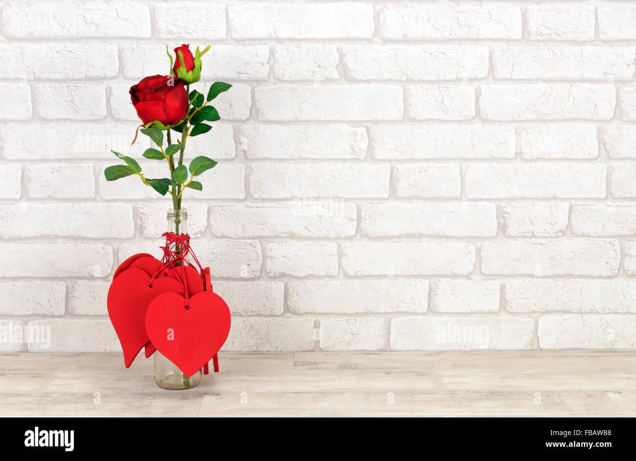 Valentine Herzen und rote Rosen in Glasflasche platziert auf einem schäbigen Holz Regal mit weiße Ziegel Wand Hintergrund Stockfoto