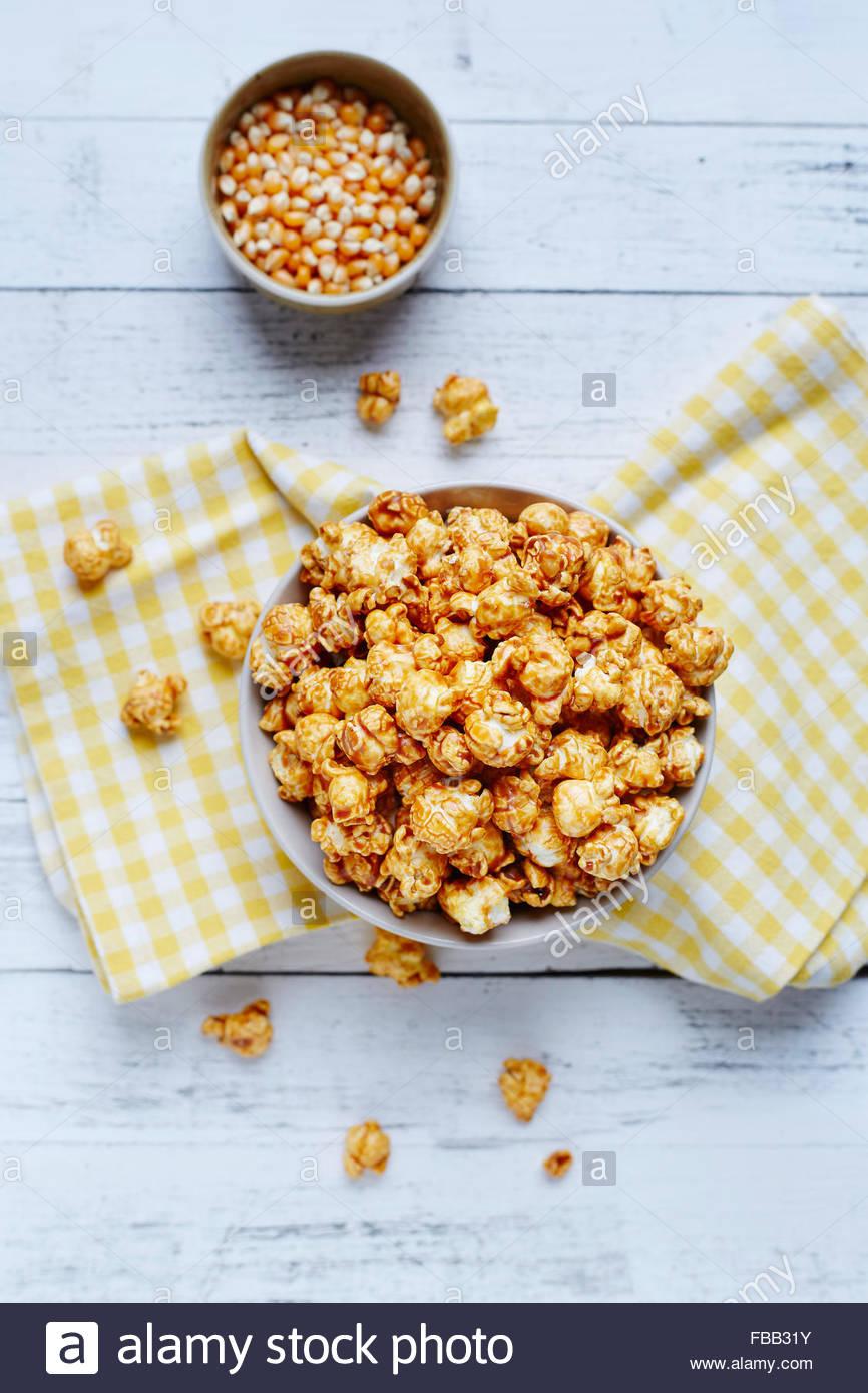 Schüssel Popcorn auf weißem rustikalen Hintergrund mit Maissaatgut Stockbild