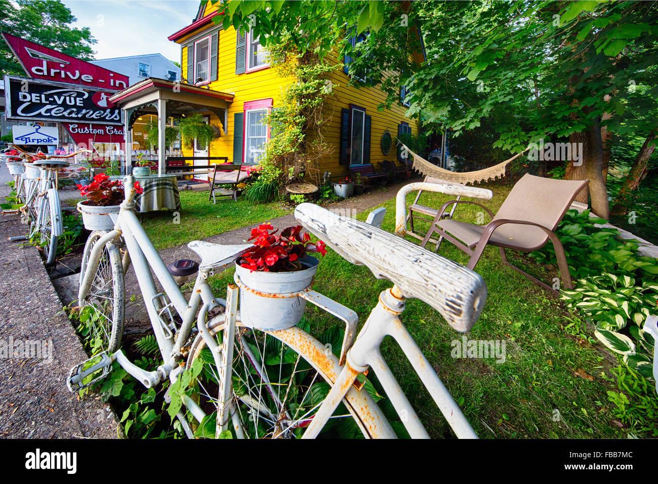 Street Art von Fahrrädern zum Zaun in ein lebendiges Gelb gemalte Haus mit alten Schildern, Lambertville, New Stockbild