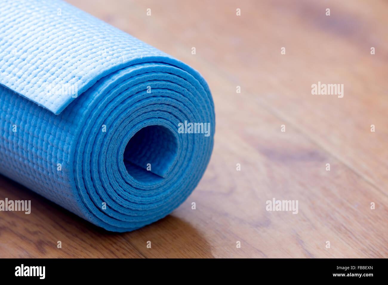 Nahaufnahme des gefalteten blauen rutschfeste Yoga, Pilates Matte auf dem Boden. Gesundes Leben, halten Sie Fit Stockbild