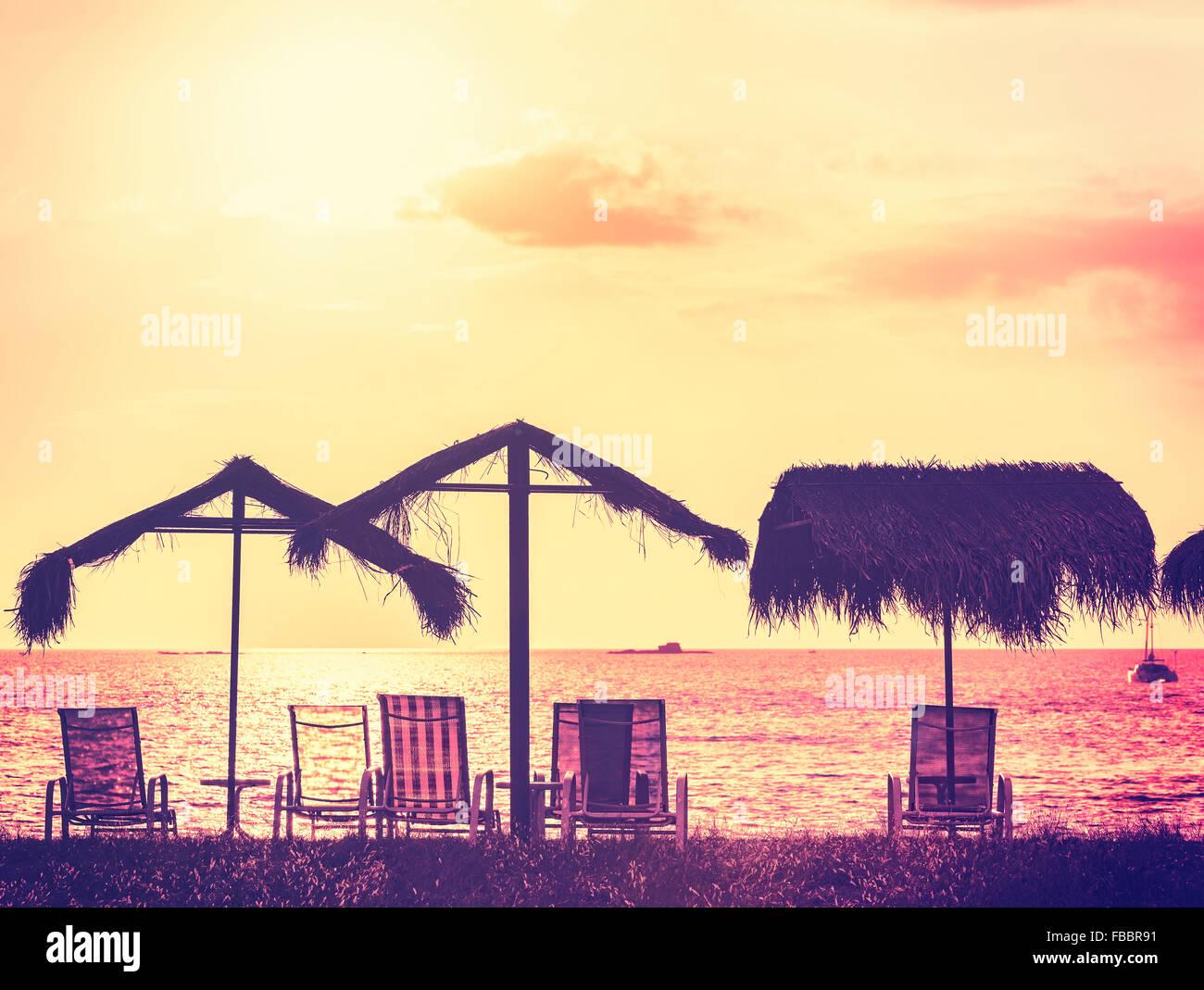 Vintage getönten Liegestühle und Sonnenschirme am Sonnenuntergang, Ferien-Hintergrund. Stockbild