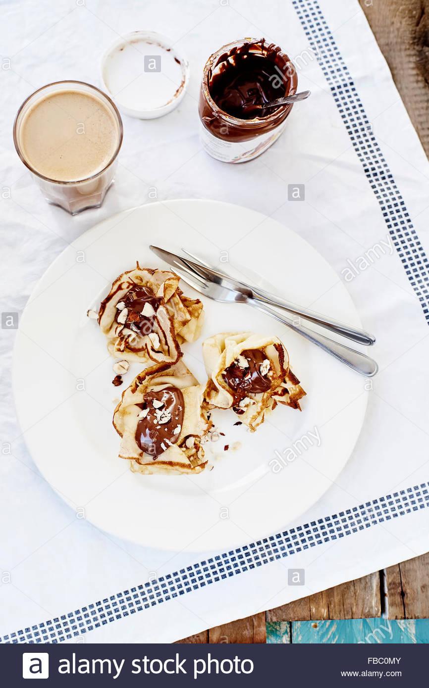 Palatschinken mit Schokolade und Kaffee auf weißem Textil outdoor Stockbild
