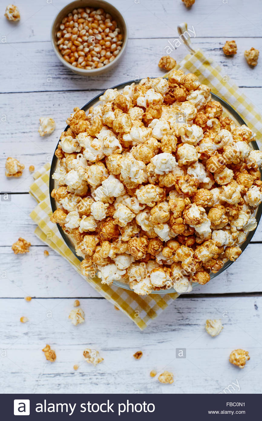 Große Schüssel Popcorn auf weißem rustikalen Hintergrund mit Maissaatgut Stockbild