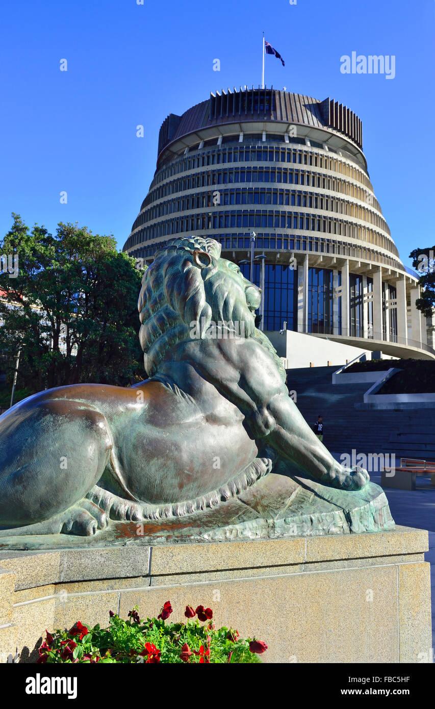 eines der zwei bronzenen Löwen auf Wellington s Kenotaph mit Parlament (Bienenstock) hinter zentrale Wellington Stockbild