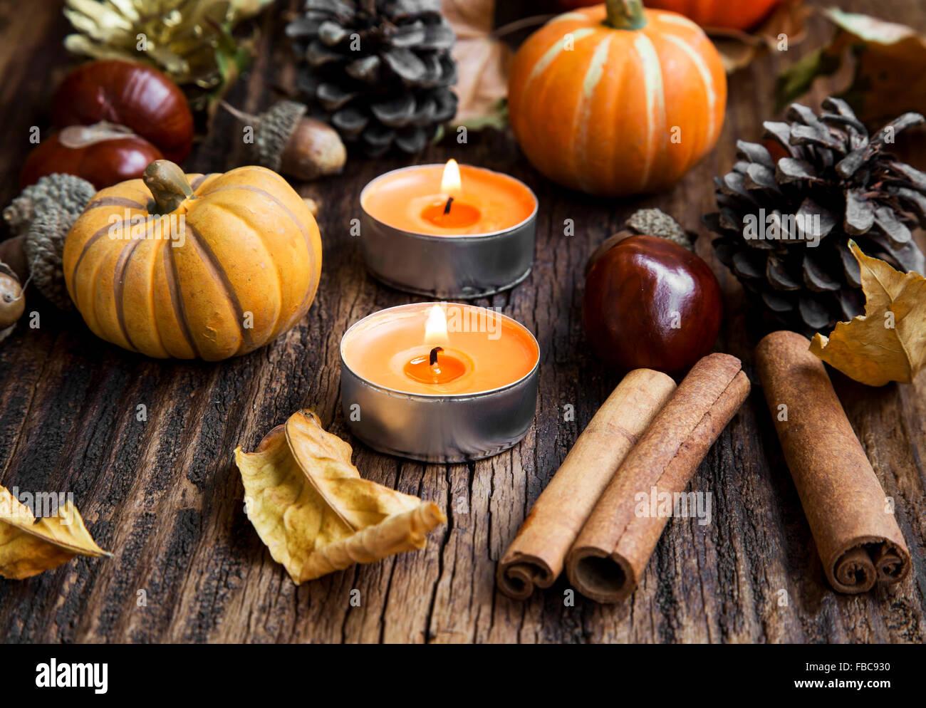 Herbst-Dekoration mit Kürbissen, Blätter, Kerzen, Zimtstangen, Kastanien und Eicheln Stockbild