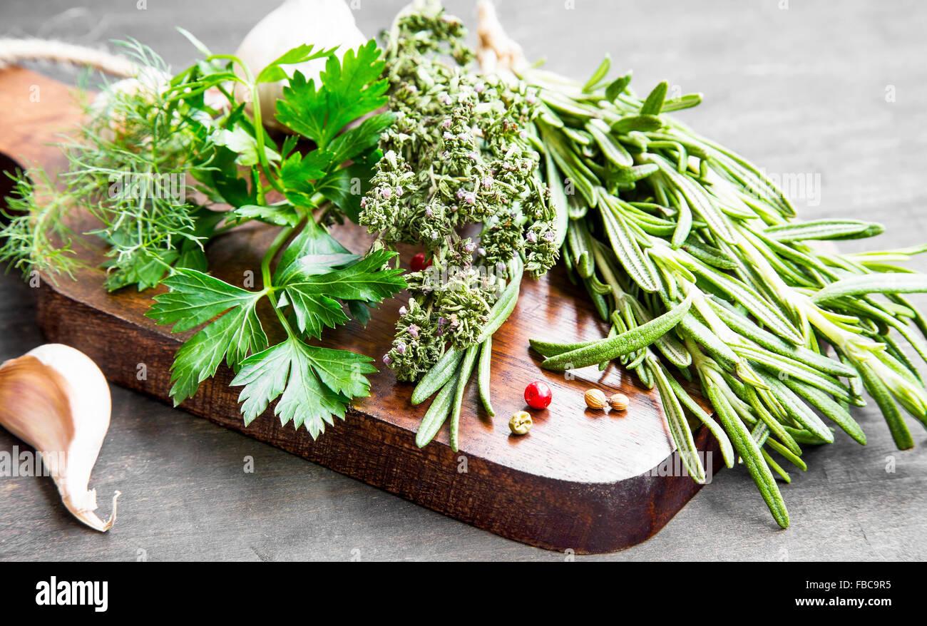 Kulinarische Kräuter Petersilie, Dill, Rosmarin und Thymian auf Holzbrett Stockbild