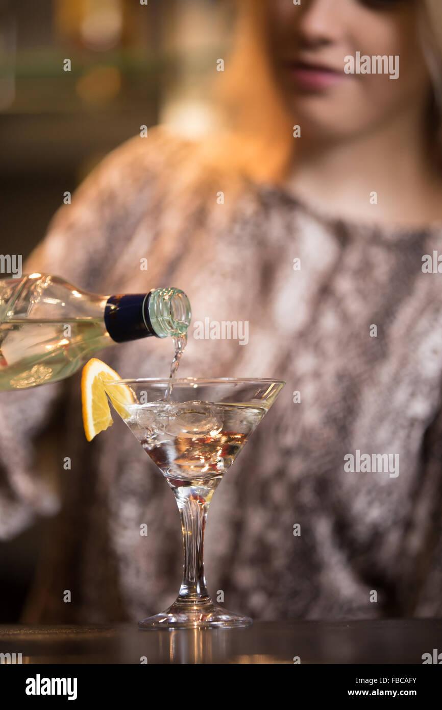 Blonden weiblichen Barkeeper Vorbereitung Alkohol Drink an der bar Theke, Holding Flasche, Gießen Drink im Stockbild