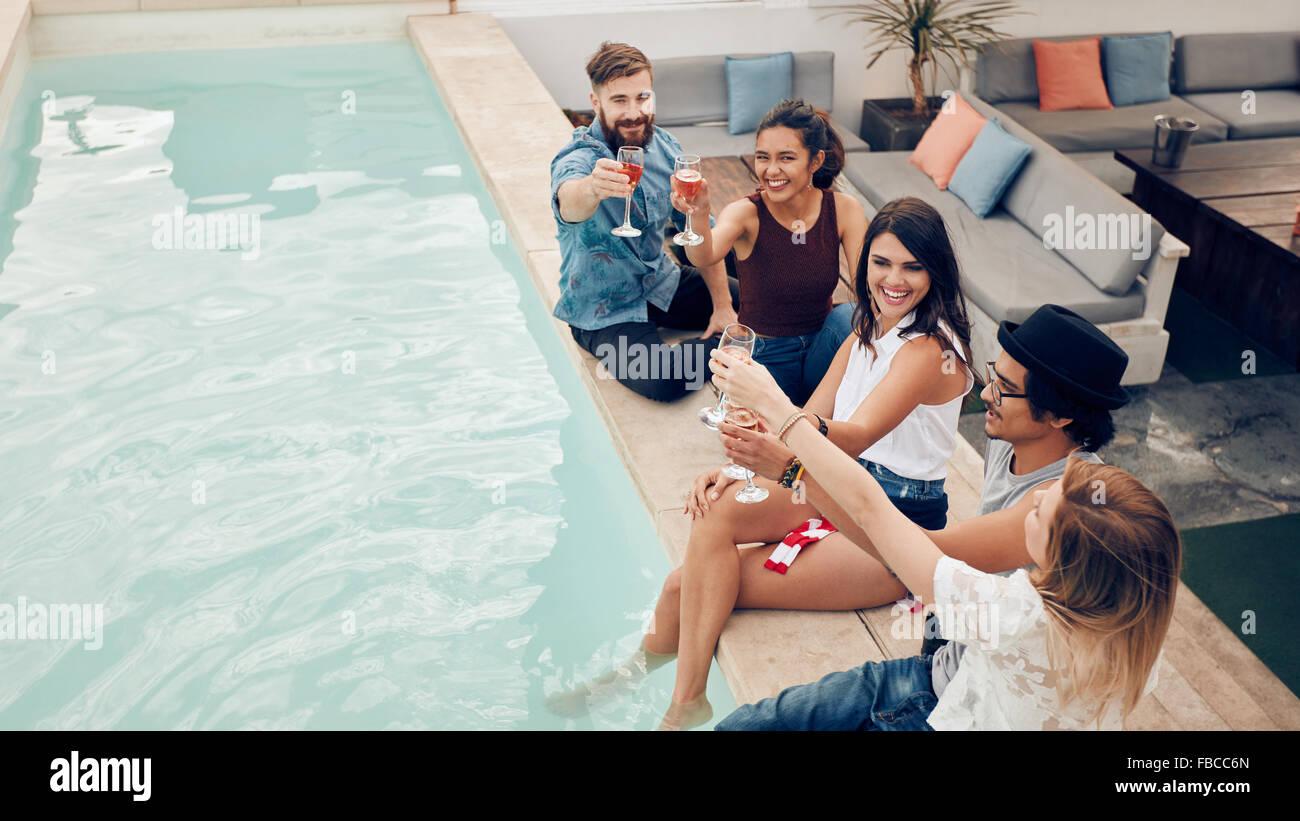 Hohen Winkel Schuss junger Menschen sitzen am Pool mit Wein und ...