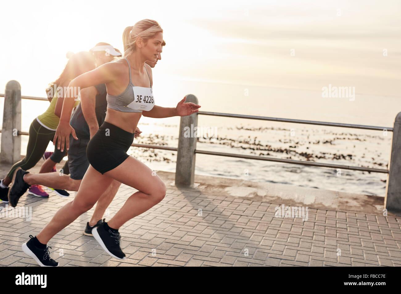 Porträt des jungen Menschen direkt an Strandpromenade laufen. Gruppe von Frauen Marathon zu laufen. Stockbild