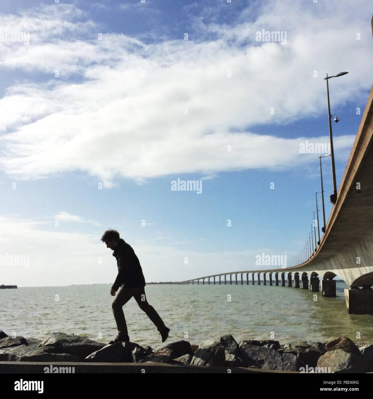 Seitenansicht der Mann zu Fuß auf Felsen auf dem Seeweg Stockbild
