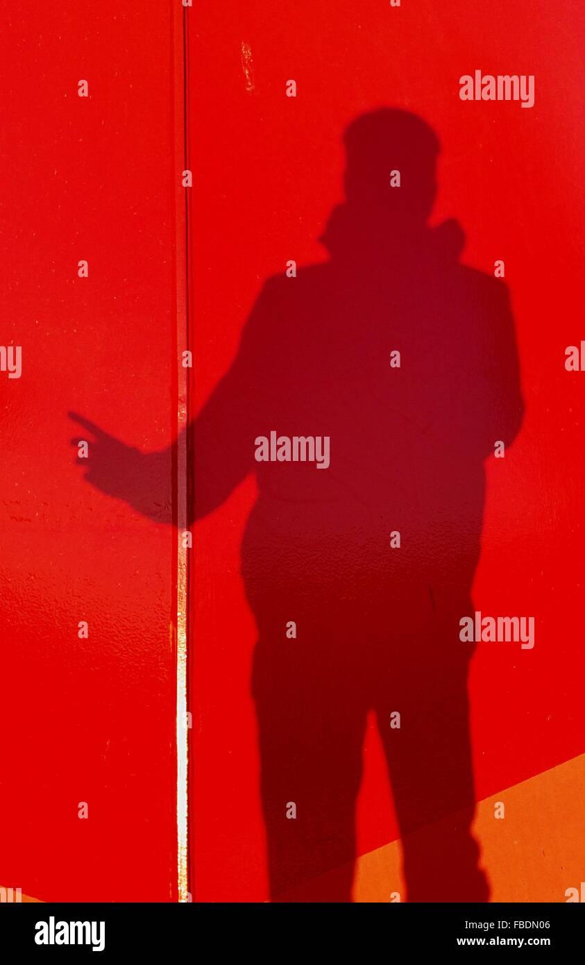 Schatten der Person auf die rote Wand Stockbild