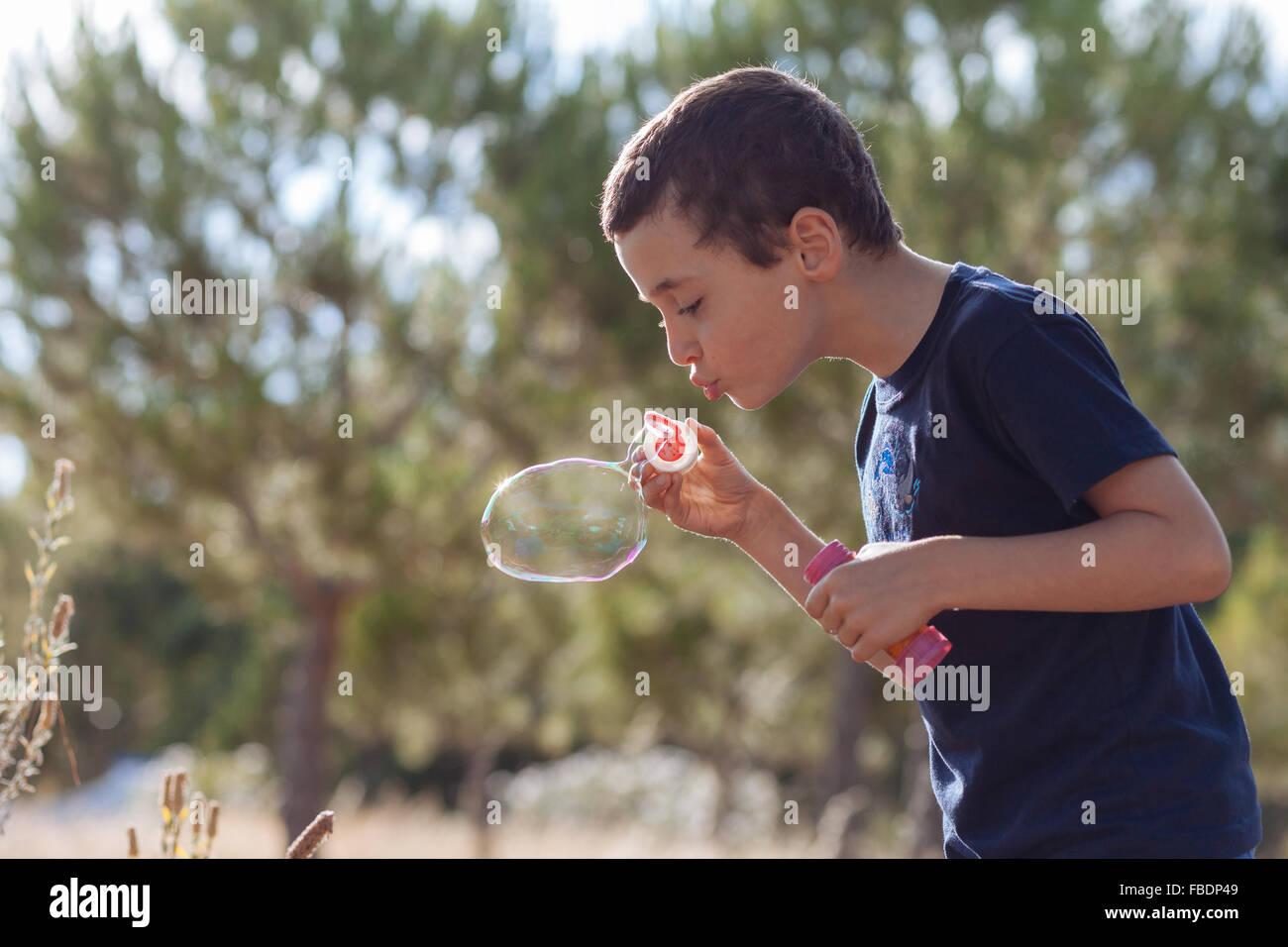 Boy bläst Seifenblasen auf Pflanzen Stockbild