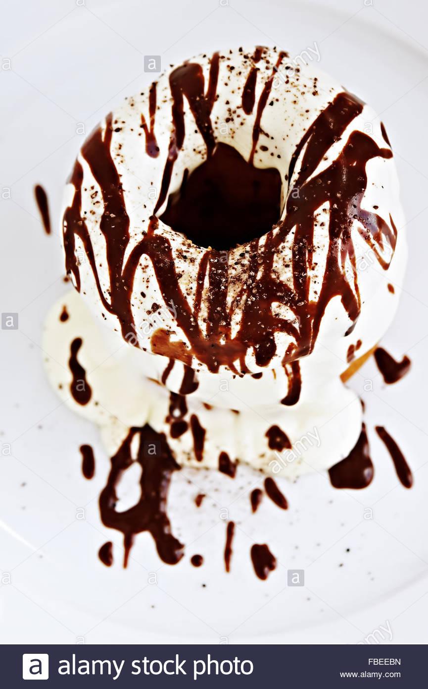 Ein Stapel von Sirup bedeckt Donuts auf weißen Teller Stockbild