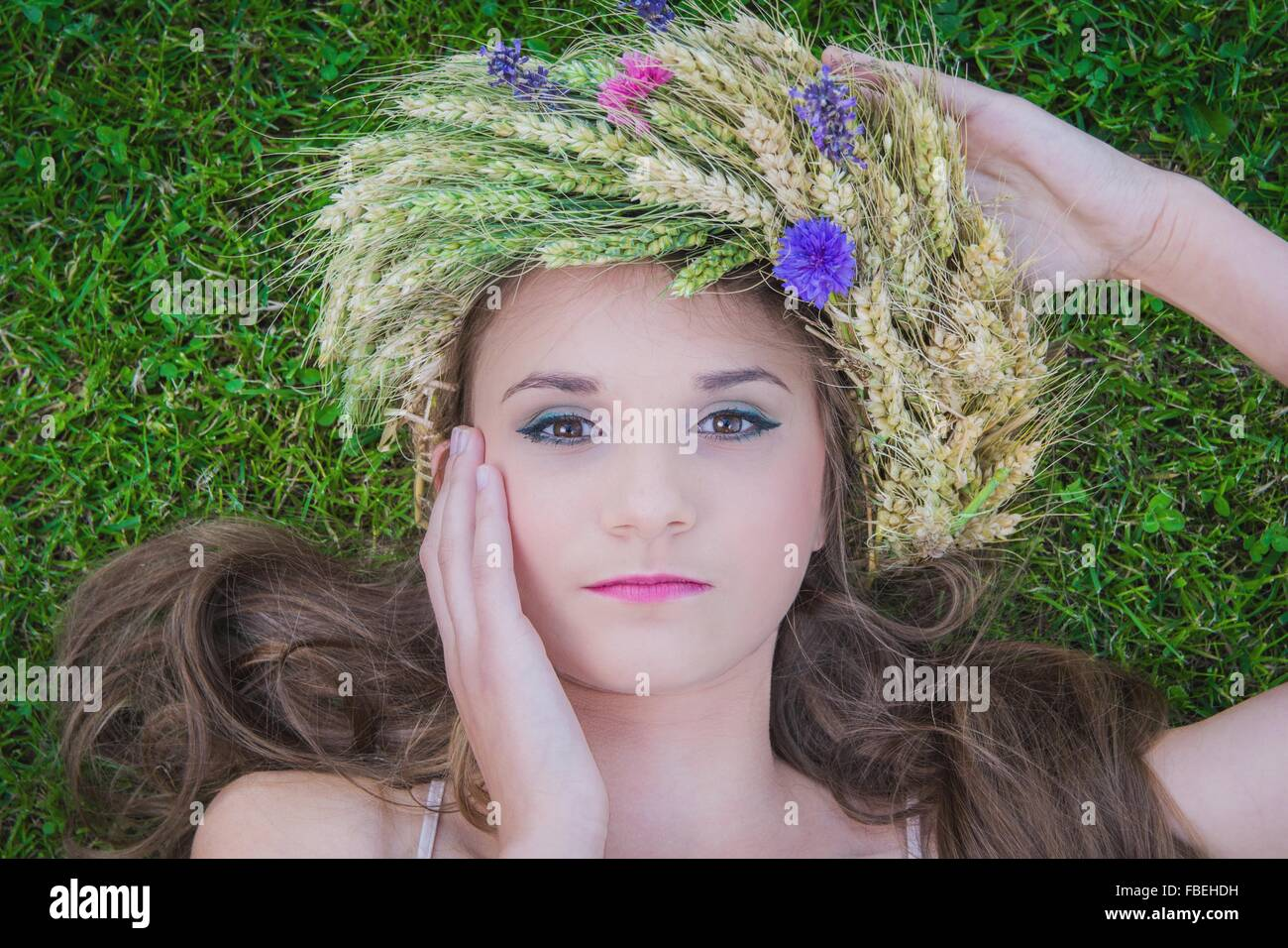 Close-up Portrait der schönen jungen Frau liegend auf dem Rasen tragen Blumen mit Hand auf Gesicht Stockbild