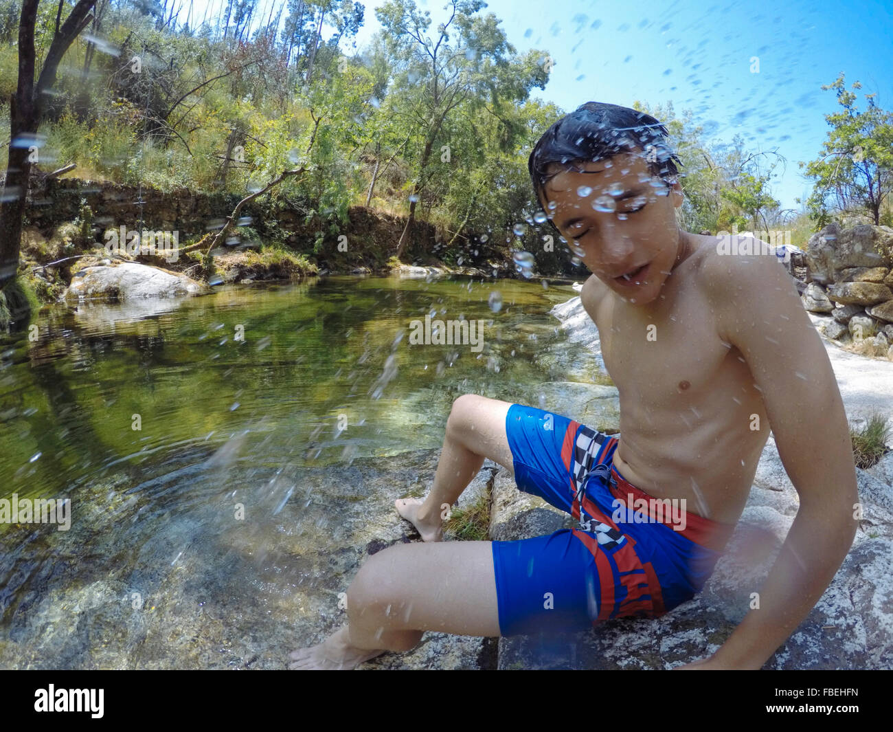Shirtless jungen mit Augen geschlossen Spritzwasser im Fluss Stockbild