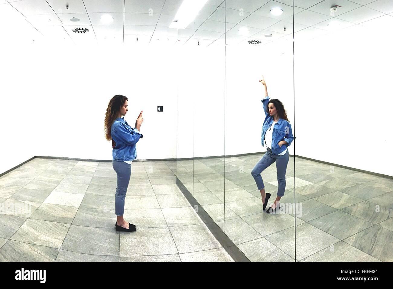 Digital erzeugte Bild Frau fotografieren sich selbst im Spiegel an beleuchteten Raum Stockbild