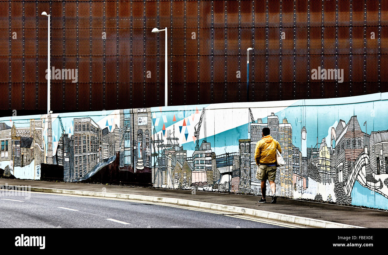 Mann zu Fuß auf Bürgersteig neben einer künstlerisch detaillierte Wandbild. Stockbild