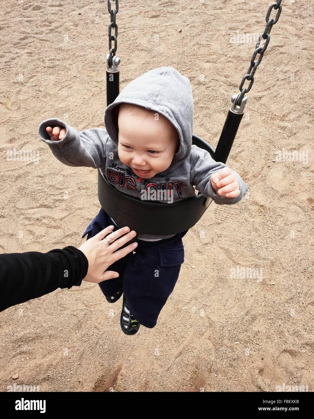 Zugeschnittenes Bild des übergeordneten Elements drängen Babyjungen In Swing im Park Stockbild