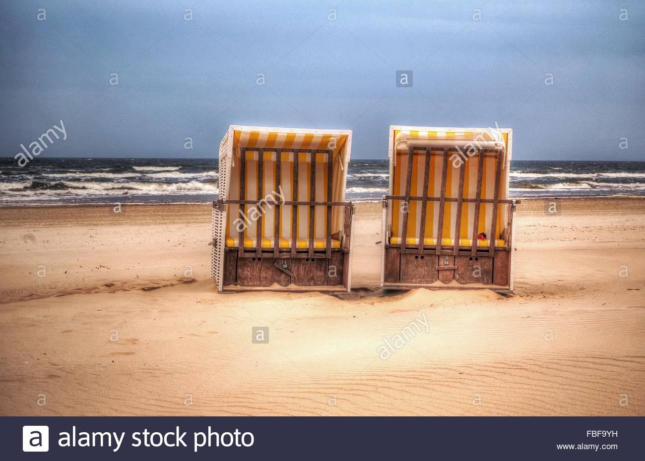 Mit Kapuze Stühle am Meer, am Strand gegen Himmel Stockbild