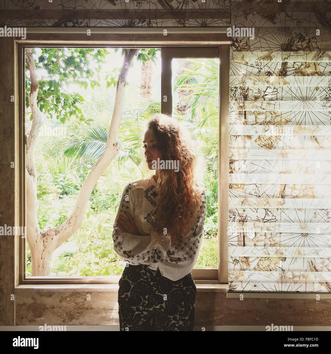 Schöne junge Frau, die Fenster zu Hause stand Stockbild