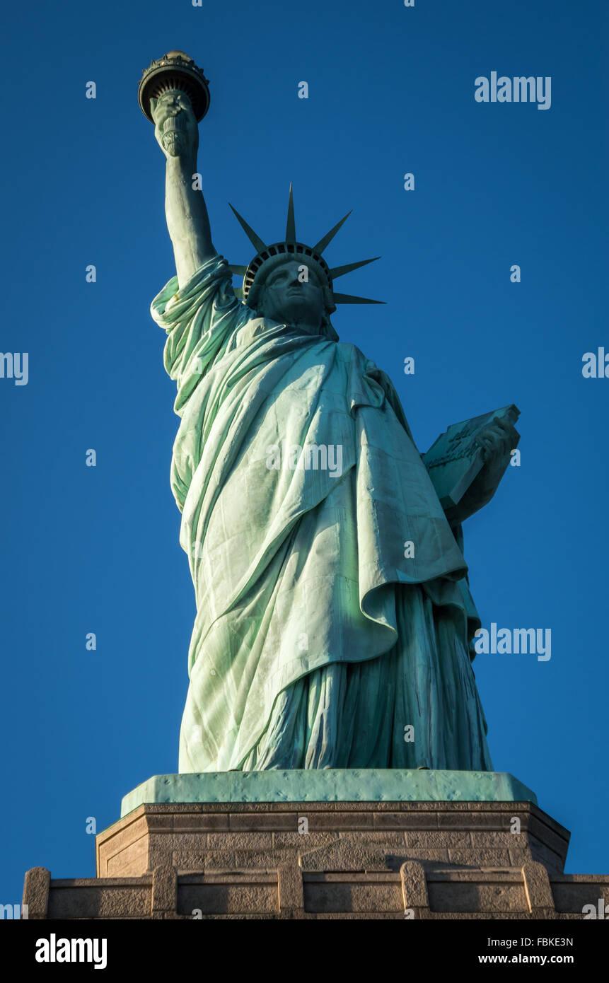 Blick auf die ganze Statue of Liberty von unten mit einem wolkenlosen blauen Himmel. Stockbild