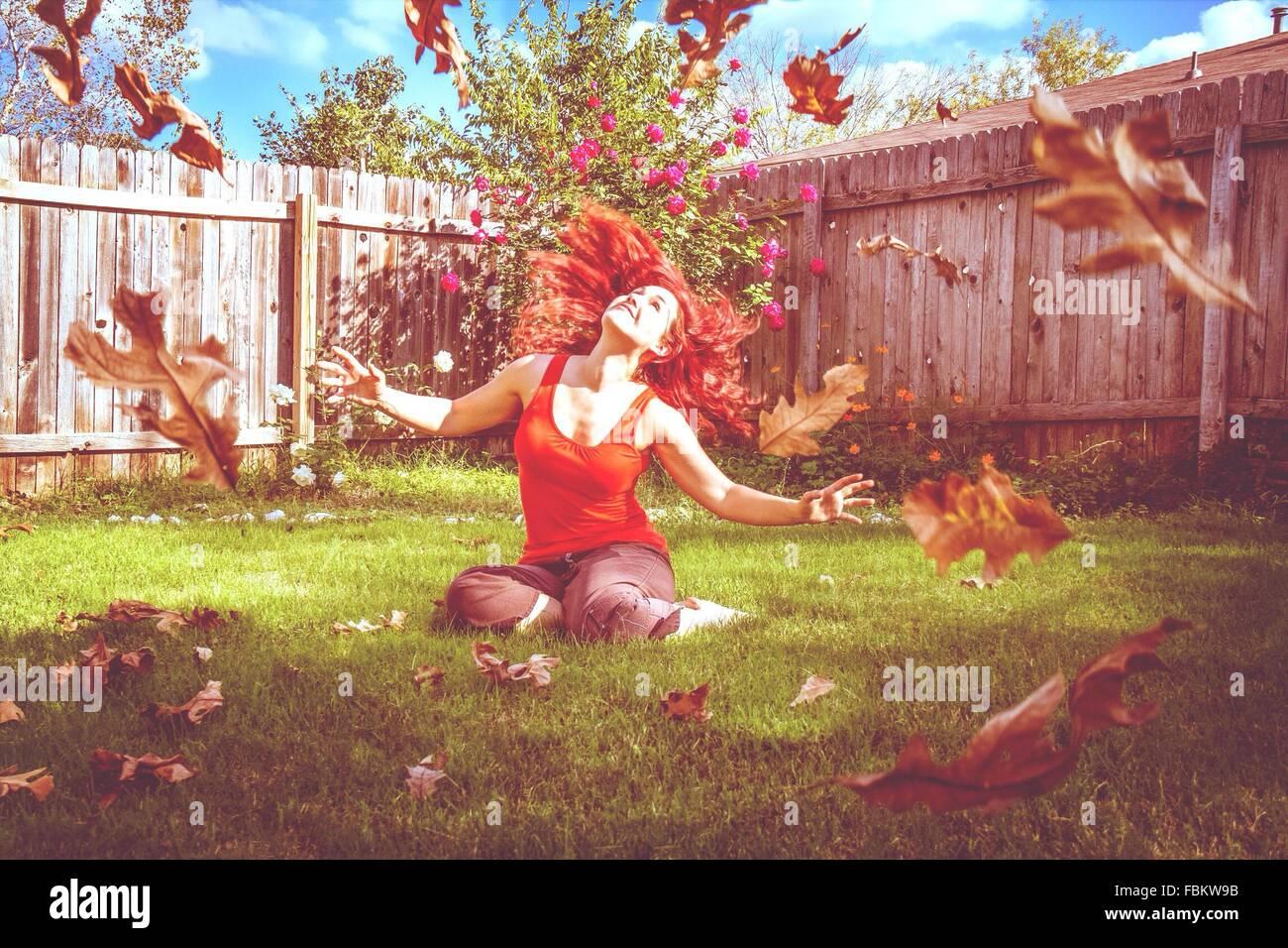 Schöne junge Frau, die fallenden Blätter zu betrachten, während Sie gemütlich auf Feld Stockbild