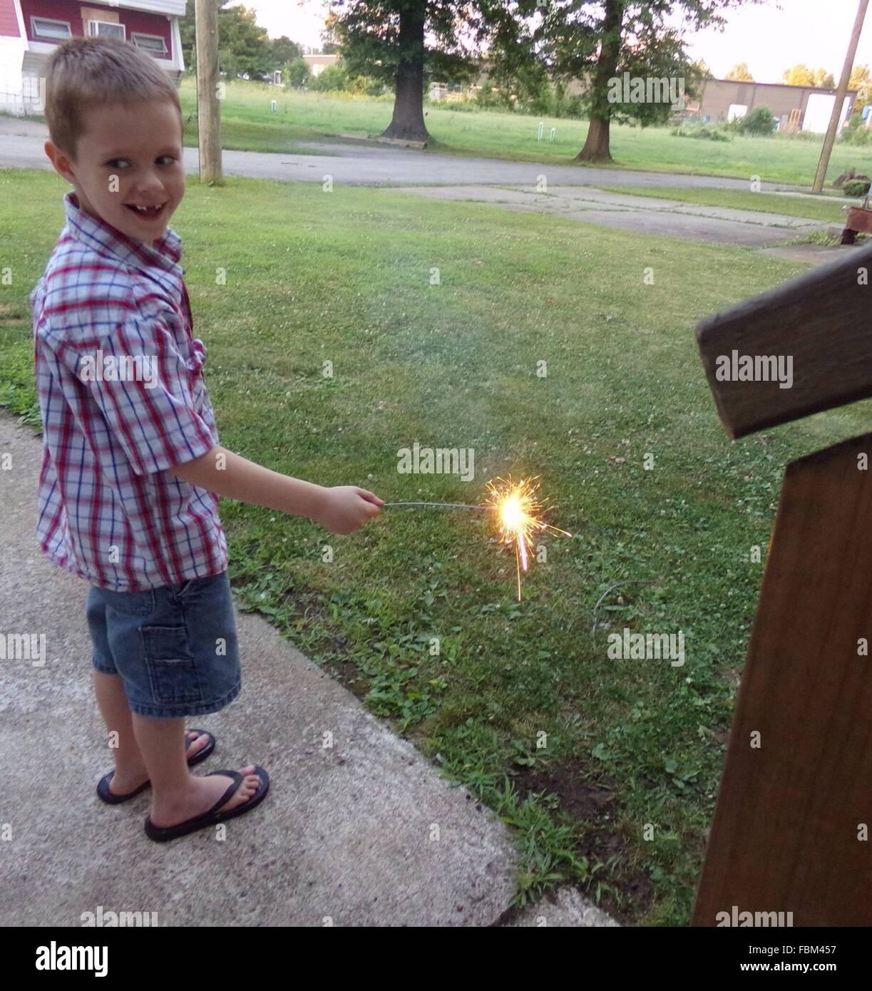 Voller Länge von fröhlicher Junge spielt mit Wunderkerze In Hof Stockbild