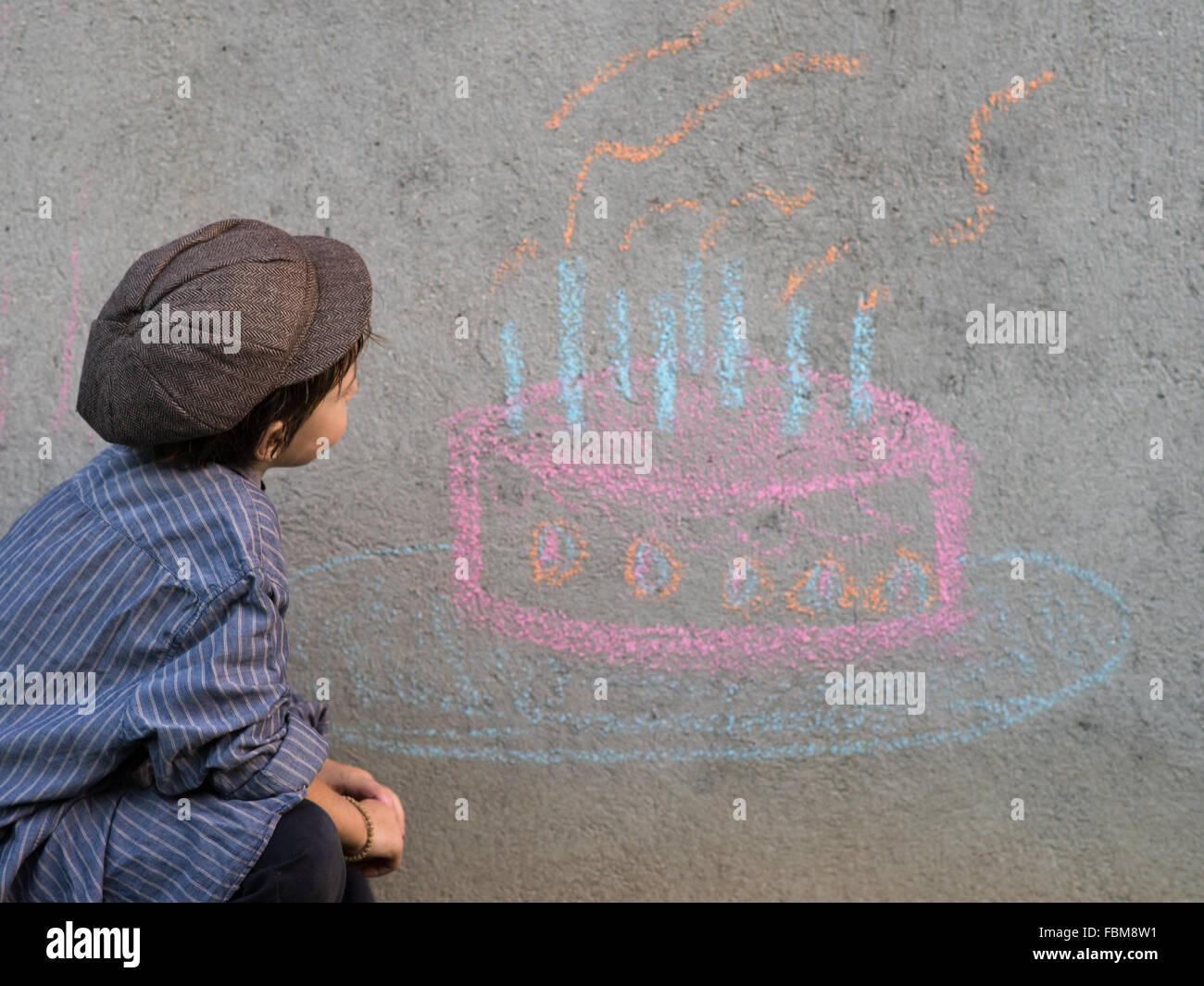 Junge Geburtstagskuchen an Wand mit Kreide zeichnen Stockfoto