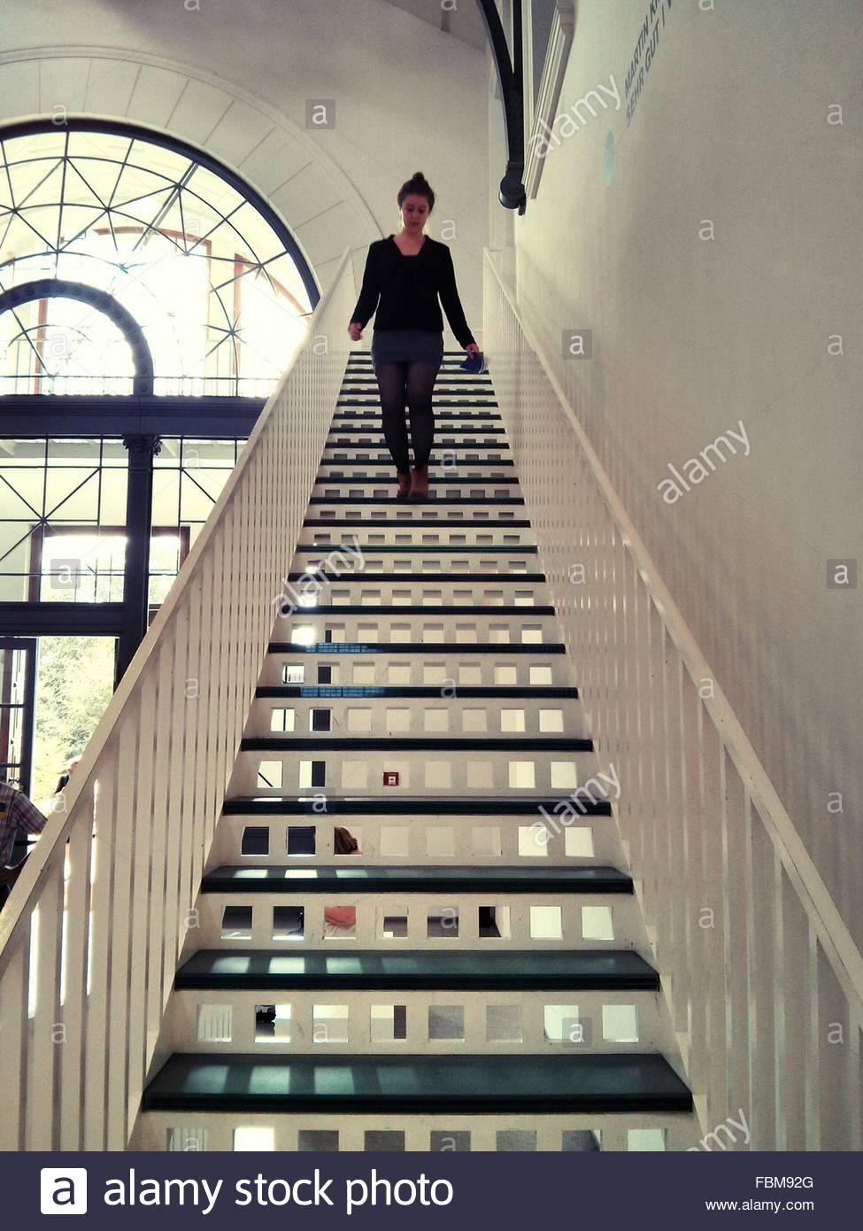 Junge Frau, die Treppe hinunter zu Hause bewegen Stockfoto