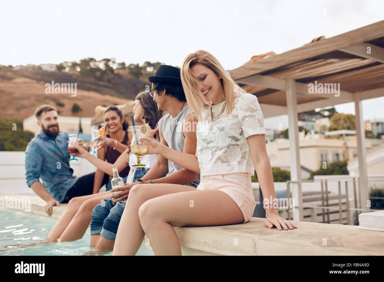 Im Freien Schuss glückliche junge Menschen feiern. Junge Männer und Frauen sitzen am Rand des Schwimmbades Stockbild
