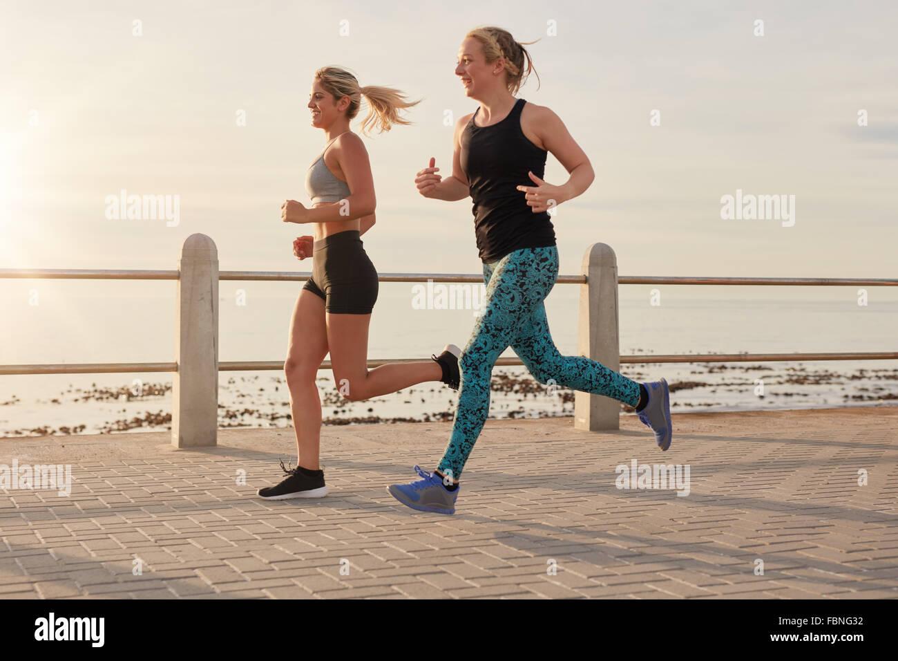 Zwei junge Frauen, die entlang der Strandpromenade. Passen Sie die jungen Läufer gemeinsam an einer Straße Stockbild