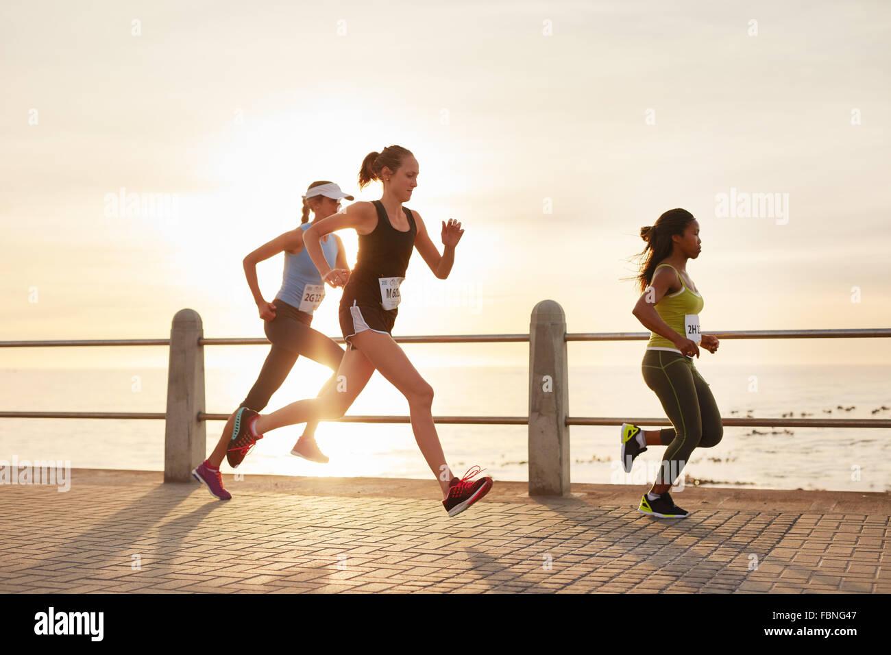 Drei junge Frauen, die auf eine Straße am Meer. Gruppe von Taucher Läufer training direkt an Strandpromenade Stockbild