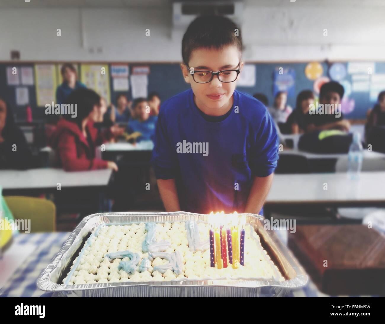 Geburtstagskind vor beleuchteten Kuchen im Klassenzimmer Stockfoto