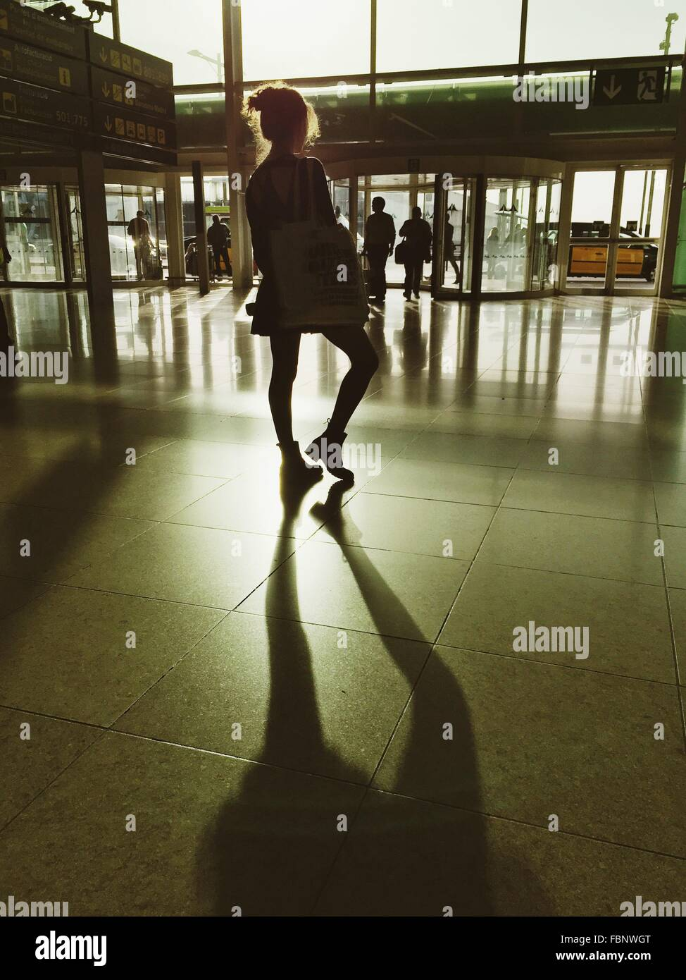 Rückansicht des jungen Frau, die am Flughafen Stockbild
