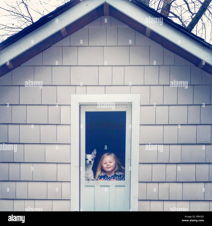 Porträt der niedliche kleine Mädchen mit Hund vor die Tür des Hauses Stockbild