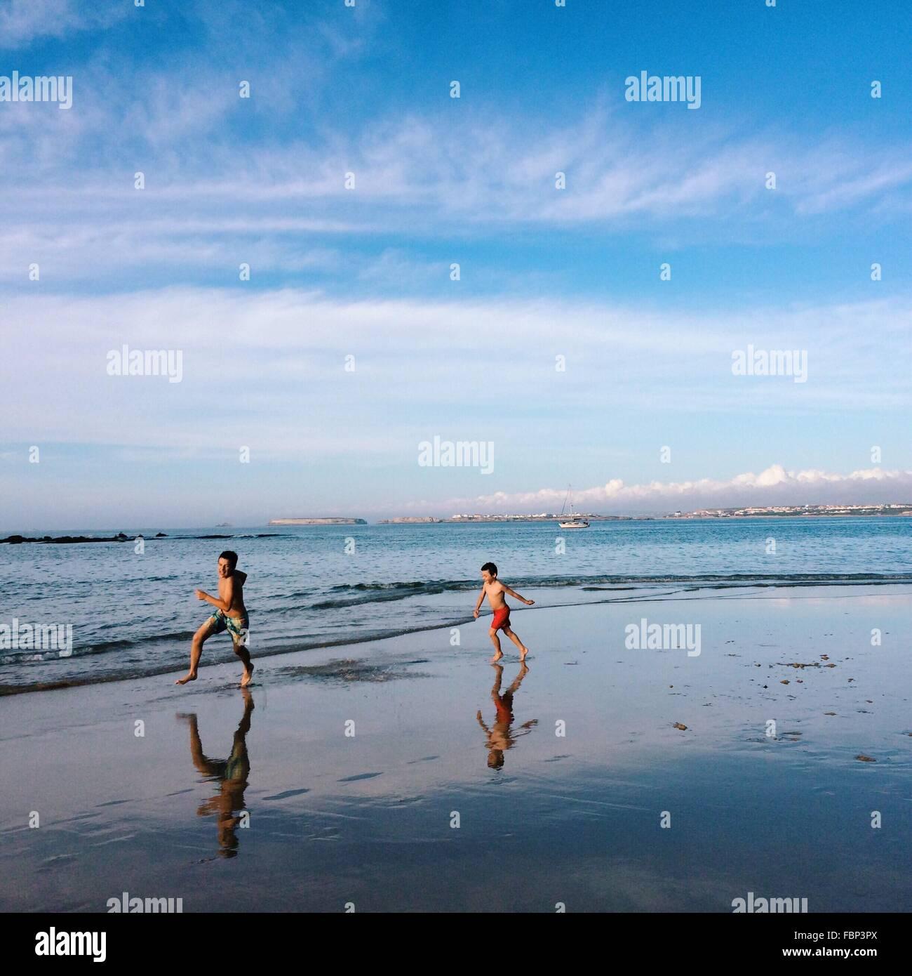 Zwei jungen laufen am Strand Stockbild