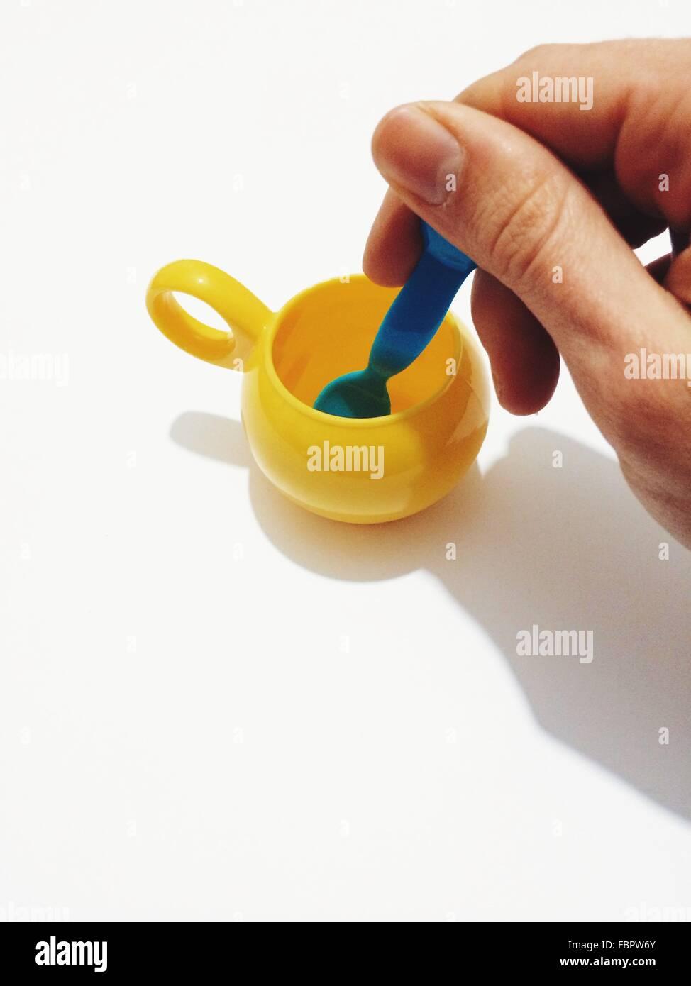 Bild des Mannes mit Spielzeug Milchtopf und Teelöffel vor weißem Hintergrund abgeschnitten Stockbild