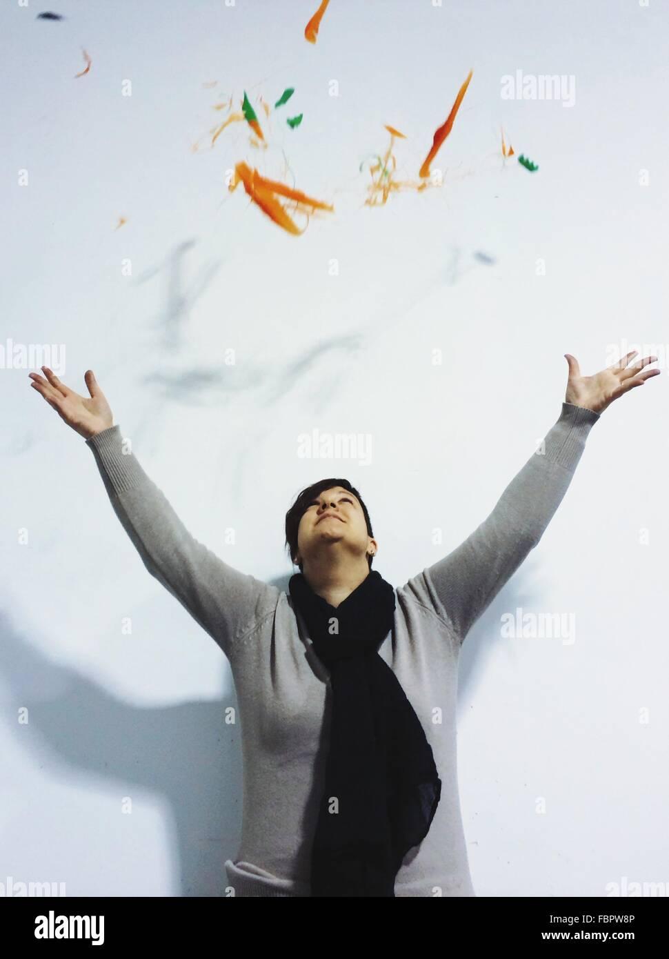 Junge Frau wirft farbige Partikel vor weißem Hintergrund Stockbild