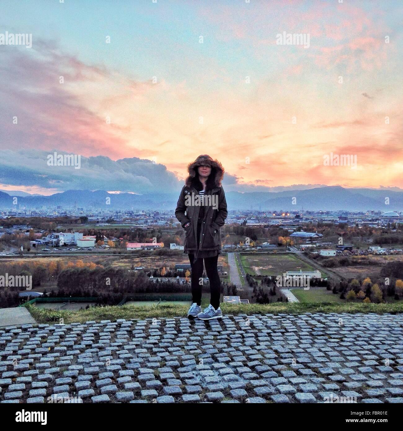 Gesamte Länge der Frau In Kapuzenjacke stehend gegen Stadtbild während des Sonnenuntergangs Stockbild