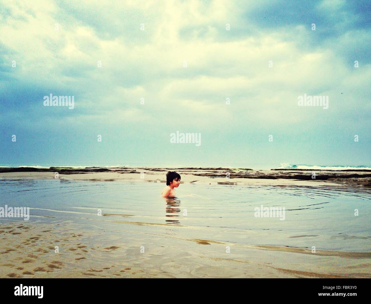 Shirtless jungen Schwimmen im Meer Stockbild